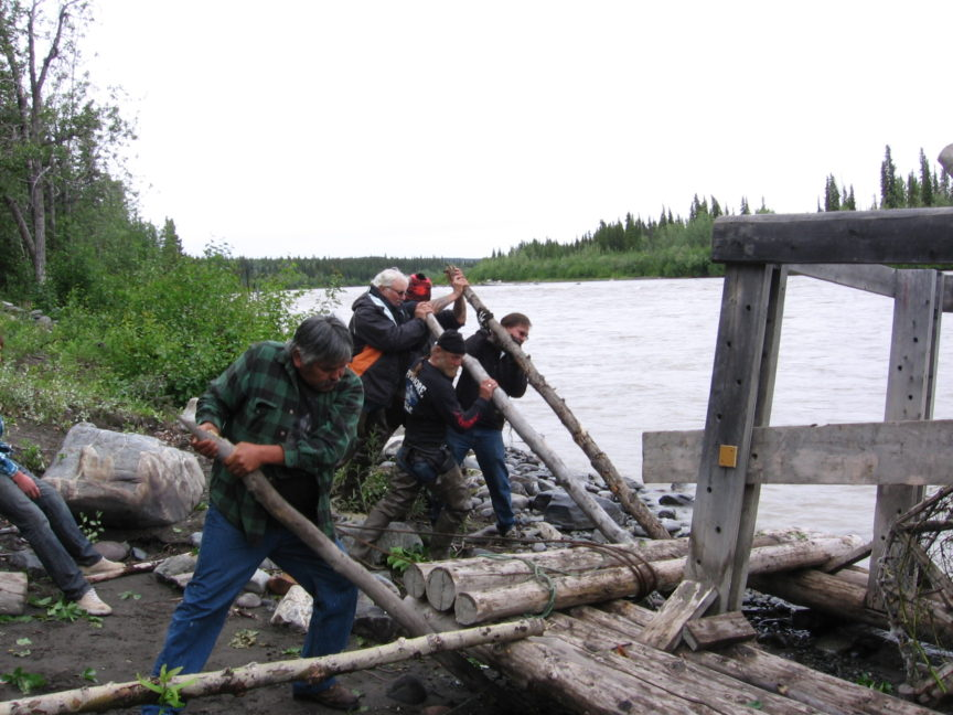 Members of a Euro-American motorcycle club work alongside citizens of the Athabascan Nation to launch a fish wheel in the Copper River, Alaska.